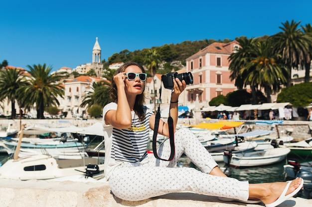 Atrakcyjna kobieta na wakacjach w europie nad morzem na rejs robienia zdjęć w aparacie