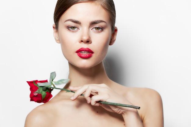 Atrakcyjna kobieta nagie ramiona czerwone usta jasne skóry kwiat róży przycięty widok jasnym tle