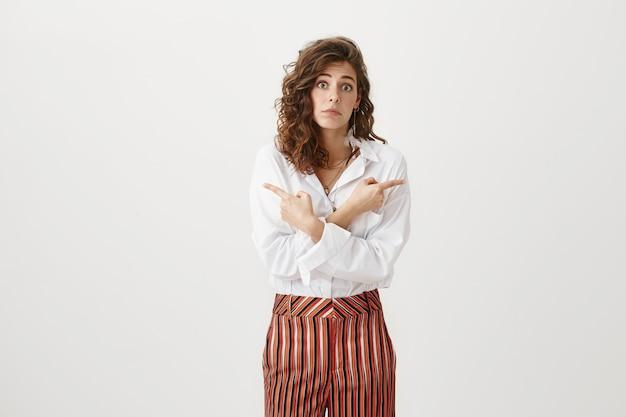 Atrakcyjna kobieta niezdecydowana, wskazująca bokiem, potrzebuje pomocy w wyborze