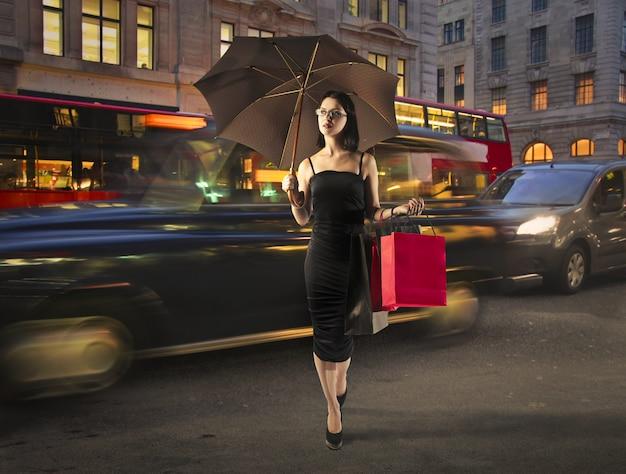 Atrakcyjna kobieta nocą z torba na zakupy