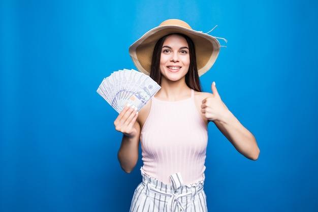 Atrakcyjna kobieta nosić w słomkowym kapeluszu pokazując banknoty 100 usd, kciuk w górę, odizolowane na niebieskiej ścianie.