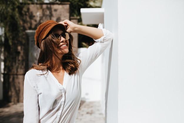 Atrakcyjna kobieta o ciemnych blond włosach w czapce i jasnej bluzce oparła się o ścianę białego budynku.