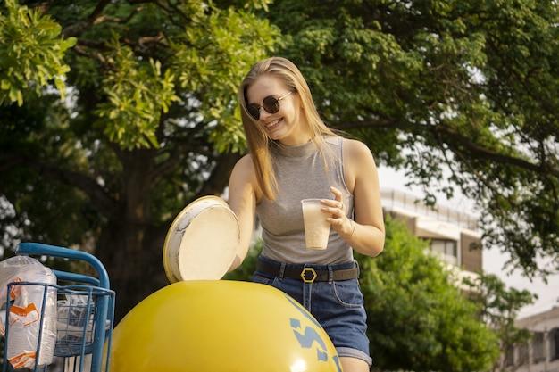 Atrakcyjna kobieta o mrożonej kawie podczas spaceru po parku