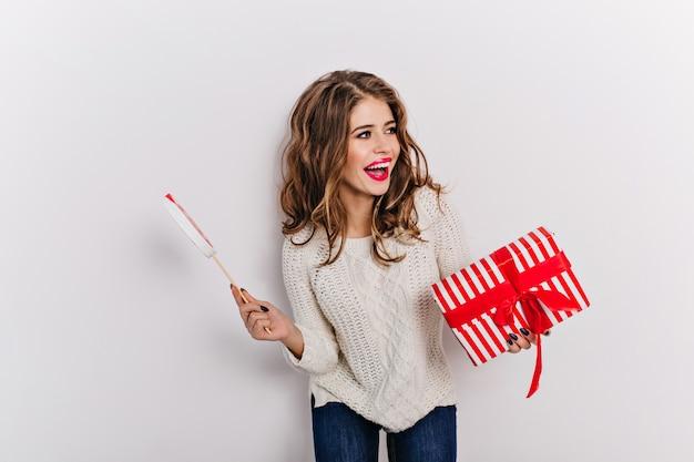 Atrakcyjna kobieta o ślicznym wyglądzie, ubrana w biały ciepły top i mom jeans z prezentem świątecznym. portret uśmiechnięty model długowłosy