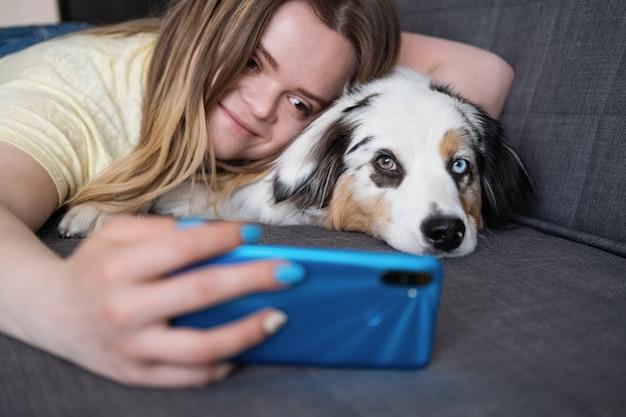 Atrakcyjna kobieta obejmuje owczarka australijskiego, robi selfie telefonem