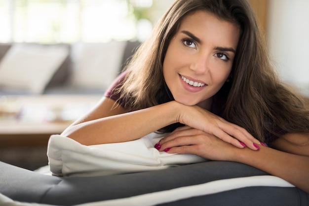 Atrakcyjna kobieta odpoczywa w swoim salonie
