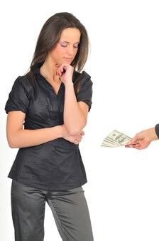 Atrakcyjna kobieta patrzy na dolary w ręku. dziewczyna pozuje w szarą bluzkę i spodnie z ręką w pobliżu twarzy