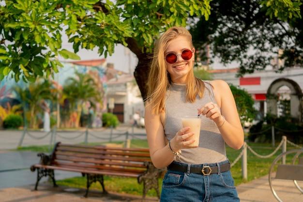 Atrakcyjna kobieta pijąca mrożoną kawę podczas spaceru po parku