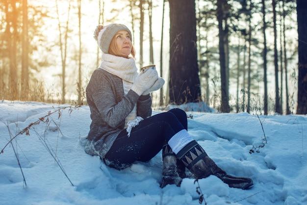 Atrakcyjna kobieta pije gorącą herbatę na świetle słonecznym w zimie