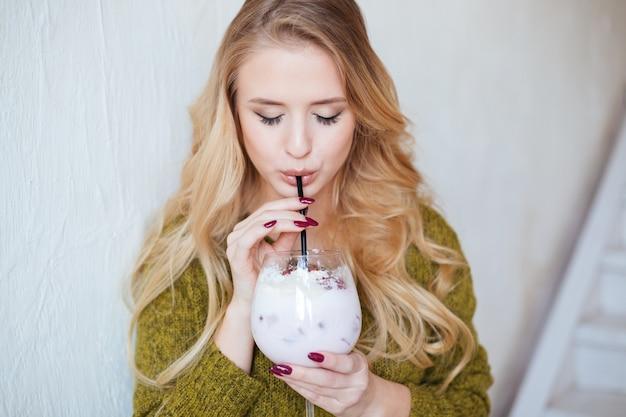 Atrakcyjna kobieta pije koktajl w restauracji