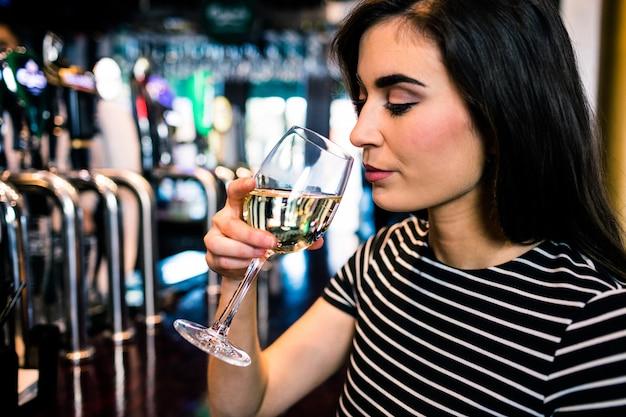 Atrakcyjna kobieta pije wino w barze
