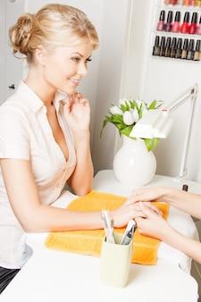 Atrakcyjna kobieta po manicure w salonie