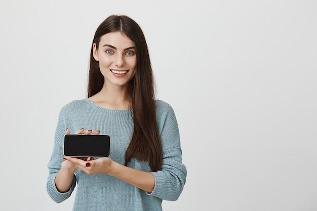 Atrakcyjna kobieta pokazuje ekran smartfona i uśmiecha się, polecam aplikację