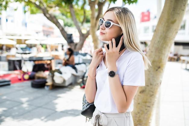 Atrakcyjna kobieta pozuje podczas rozmowy na telefon na świeżym powietrzu w lecie