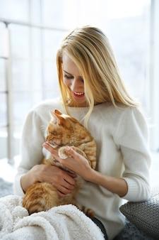 Atrakcyjna kobieta pozuje z czerwonym kotem