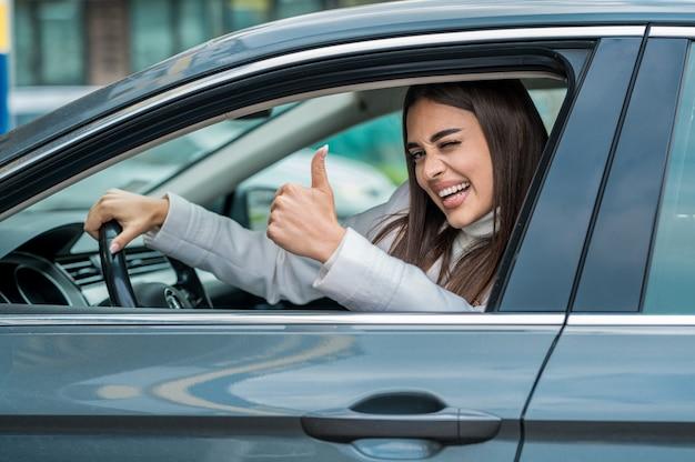 Atrakcyjna kobieta pozuje za kierownicą swojego samochodu