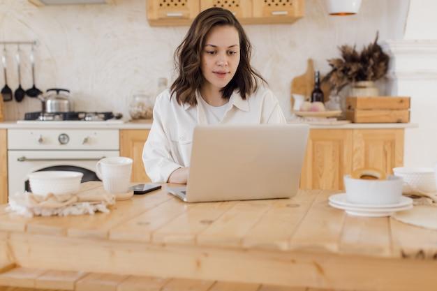 Atrakcyjna kobieta pracująca na laptopie siedzi przy biurku w przytulnym salonie bizneswoman siedzi w miejscu pracy...