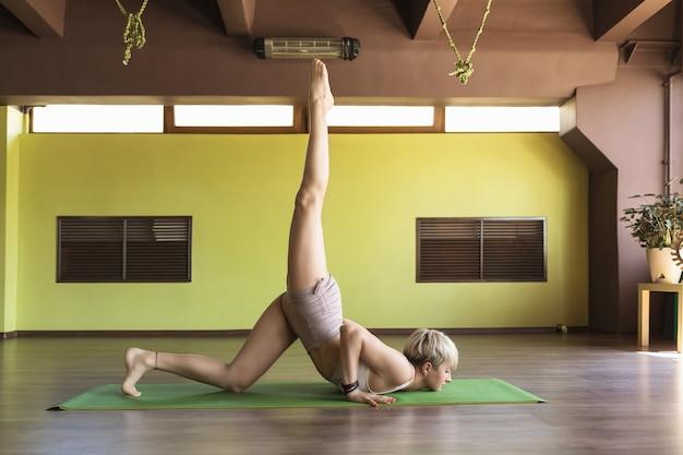 Atrakcyjna kobieta praktykuje jogę w krótkich spodenkach i krótkiej koszulce