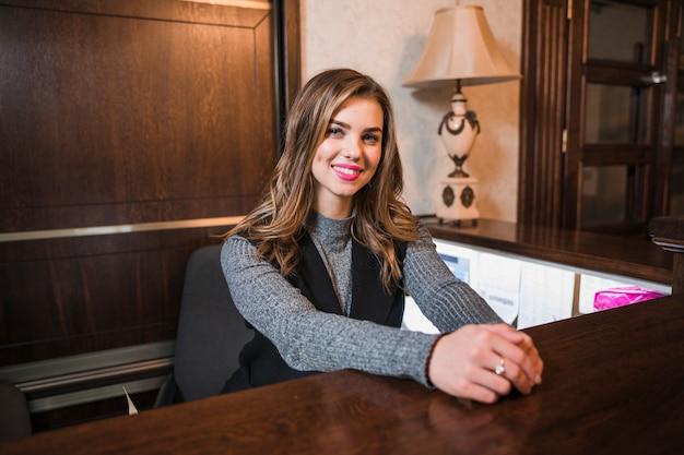 Atrakcyjna kobieta przy biurkiem patrzeje kamerę