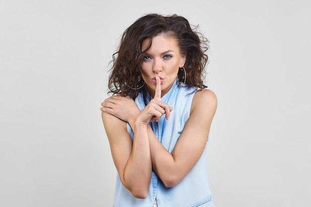 Atrakcyjna kobieta przyłożyła palec wskazujący do ust