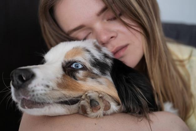 Atrakcyjna kobieta przytula się do niebieskiego merle owczarka australijskiego