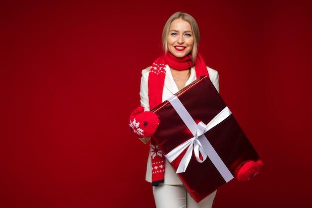Atrakcyjna kobieta rasy kaukaskiej w białym garniturze z szalikiem i rękawiczkami trzyma duży prezent na boże narodzenie z białą kokardą.