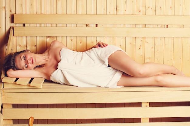 Atrakcyjna kobieta relaksująca się w drewnianej saunie