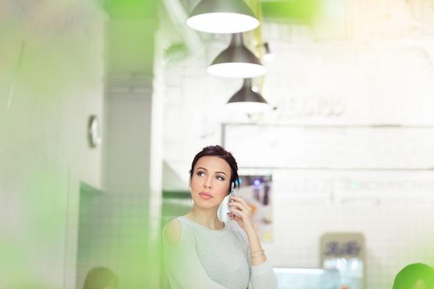 Atrakcyjna kobieta rozmawiająca przez telefon w kawiarni