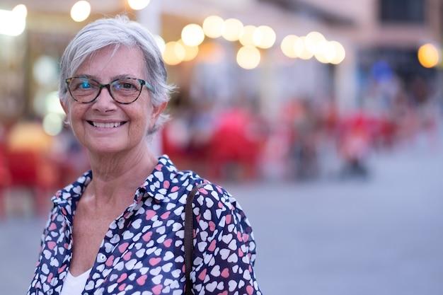 Atrakcyjna kobieta senior w odkrytym w mieście w świetle słońca, patrząc na kamery. kaukaski siwowłosy cieszący się wolnością i wakacjami