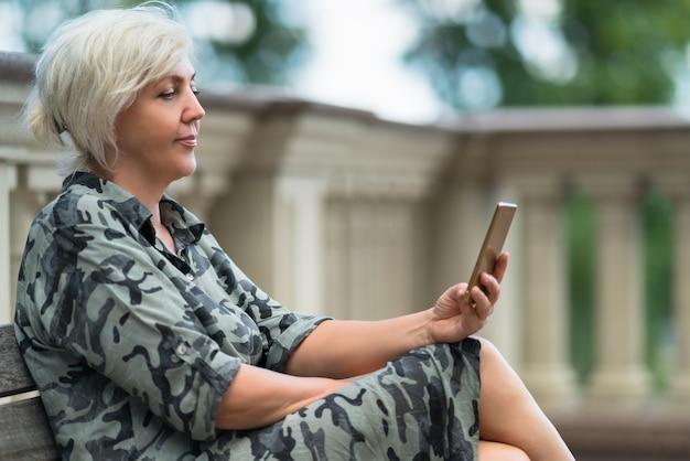 Atrakcyjna kobieta siedzi na ławce na świeżym powietrzu, czytając jej telefon komórkowy z cichym uśmiechem przyjemności w widoku z boku z bliska