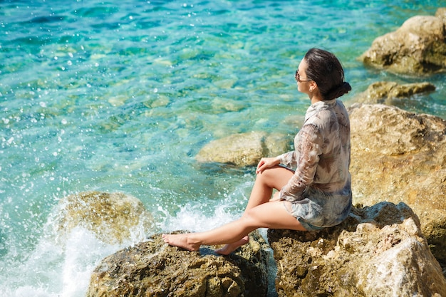 Atrakcyjna kobieta siedzi na skałach na plaży