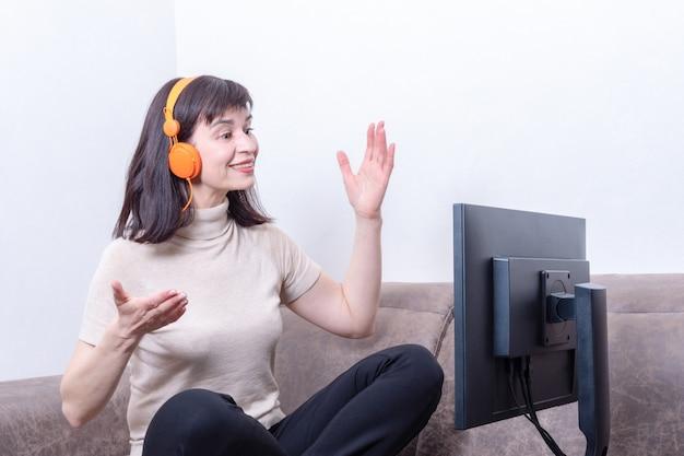 Atrakcyjna kobieta siedzi na sofie w pomarańczowych słuchawkach patrząc na monitor komputera, gestykuluje i komunikuje się online