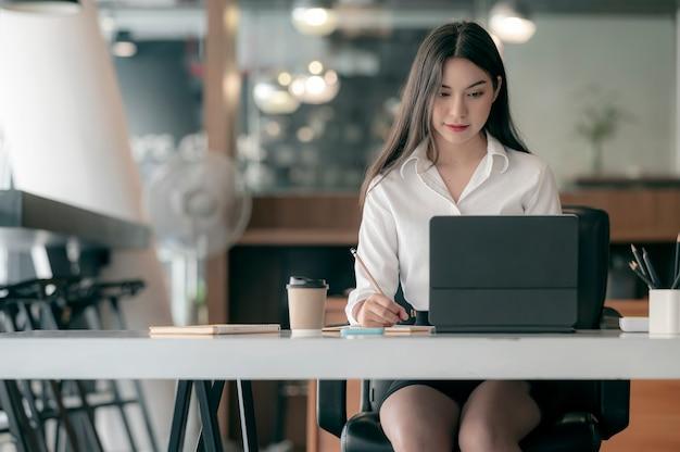 Atrakcyjna kobieta siedzi przy biurku, pisanie na notebooku i patrz? c na ekran laptopa.