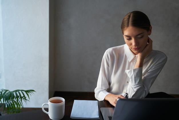Atrakcyjna kobieta siedzi przy stole i pracuje na laptopie