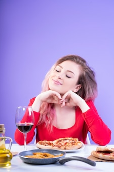 Atrakcyjna kobieta siedzi przy stole z zamkniętymi oczami
