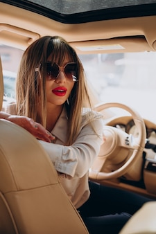 Atrakcyjna kobieta siedzi w swoim samochodzie