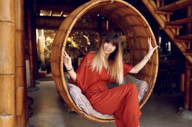 Atrakcyjna kobieta siedzi w wiszących bambusowych schodach na werandzie na świeżym powietrzu w drewnianym domku