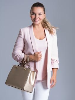 Atrakcyjna kobieta smilee trzyma złotą torebkę na białym