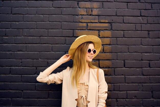 Atrakcyjna kobieta spacer na świeżym powietrzu moda lato czarny mur z cegły. zdjęcie wysokiej jakości