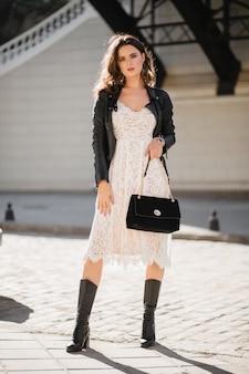 Atrakcyjna kobieta spacerująca po ulicy w modnym stroju, trzymająca torebkę, patrząc w dół, ubrana w czarną skórzaną kurtkę i białą koronkową sukienkę, wiosenno-jesienny styl