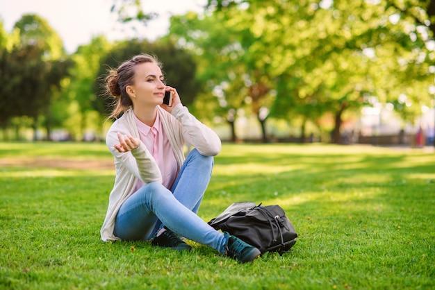Atrakcyjna kobieta spaeking na telefon komórkowy w przyjemnej atmosferze na świeżym powietrzu w parku