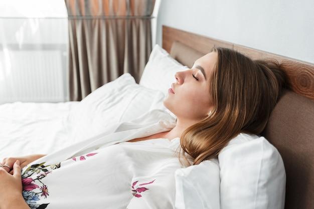 Atrakcyjna kobieta śpi w łóżku w pokoju hotelowym