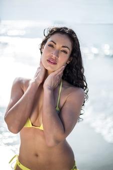 Atrakcyjna kobieta stojąca na brzegu morza w słoneczny dzień