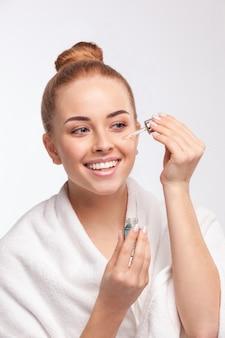 Atrakcyjna kobieta stosując leczenie na jej twarzy