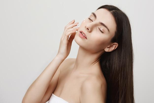 Atrakcyjna kobieta stosuje krem do twarzy, produkt przeciwstarzeniowy