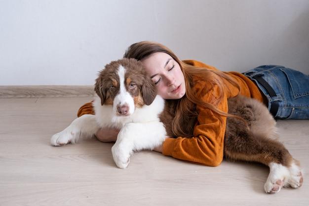 Atrakcyjna kobieta szczęśliwa przytulić piękna mały ładny owczarek australijski czerwony trzy kolory szczeniak. miłość i przyjaźń między człowiekiem a zwierzęciem.