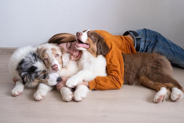 Atrakcyjna kobieta szczęśliwa przytulić trzy piękne małe słodkie owczarek australijski czerwony merle szczeniak. miłość i przyjaźń między człowiekiem a zwierzęciem.