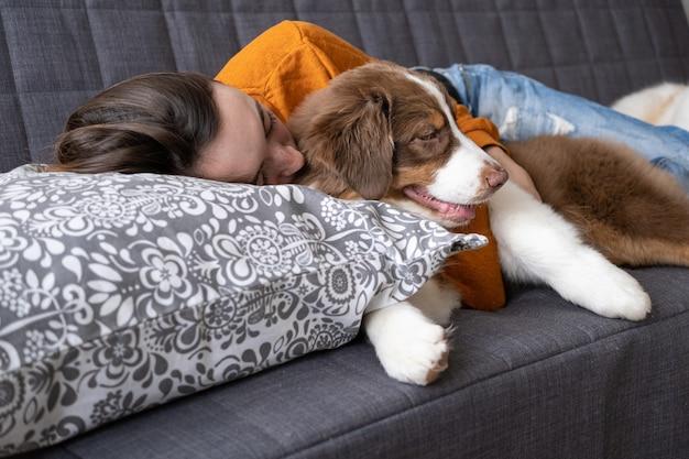 Atrakcyjna kobieta szczęśliwa spać z małym cute owczarek australijski czerwony trzy kolory szczeniak na kanapie. miłość i przyjaźń między człowiekiem a zwierzęciem.