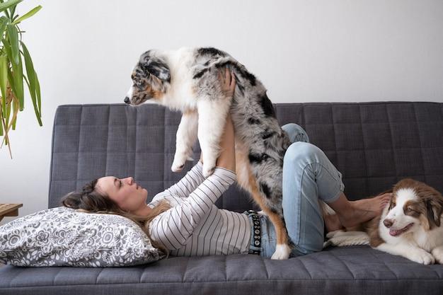 Atrakcyjna kobieta szczęśliwa trzymać piękny mały śliczny owczarek australijski blue merle szczeniak na kanapie.