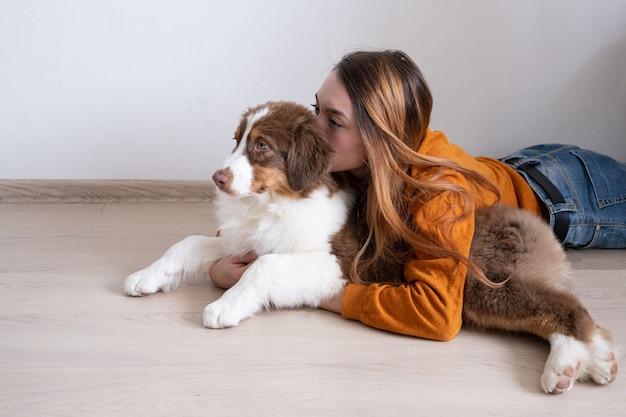 Atrakcyjna kobieta szczęśliwa uścisk pocałunek piękna mały ładny owczarek australijski czerwony trzy kolory szczeniak. miłość i przyjaźń między człowiekiem a zwierzęciem.